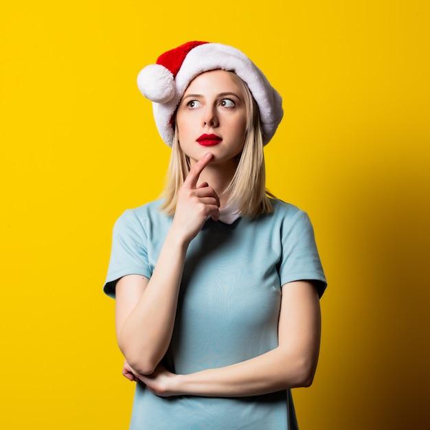 Chica rubia con vestido azul y sombrero de santa claus en espacio amarillo