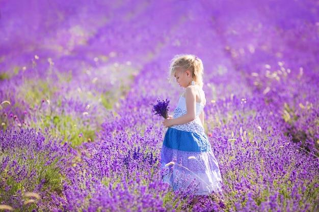 Chica rubia en el vestido de color en el campo od lavanda con un pequeño bouqet en sus manos
