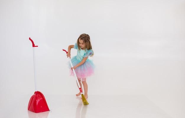 Una chica rubia con un vestido de fiesta hace la limpieza sobre un fondo blanco con un lugar para el texto