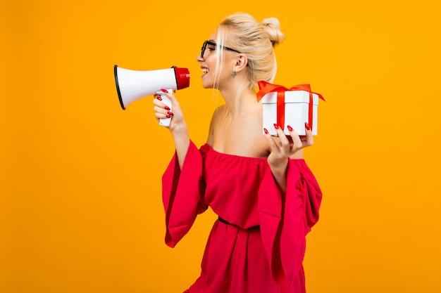 Chica rubia con un vestido rojo habla de regalos con un megáfono y una caja de regalo en las manos sobre una pared amarilla