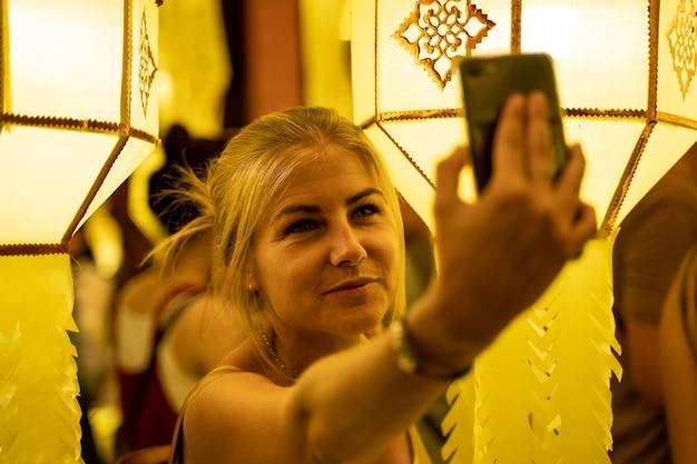 Chica rubia en un vestido sin tirantes rodeado de farolillos chinos en la noche haciendo una selfie