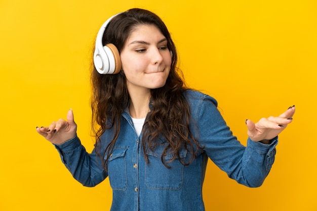 Chica rusa adolescente aislada sobre fondo amarillo escuchando música y bailando