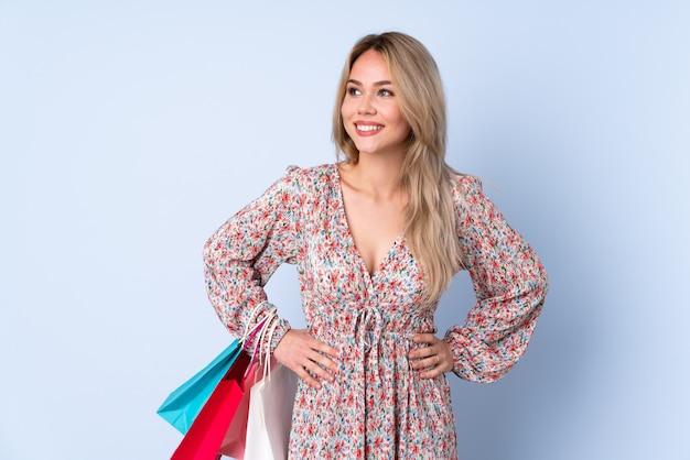 Chica rusa adolescente con bolsa de compras en la pared azul posando con los brazos en la cadera y sonriendo