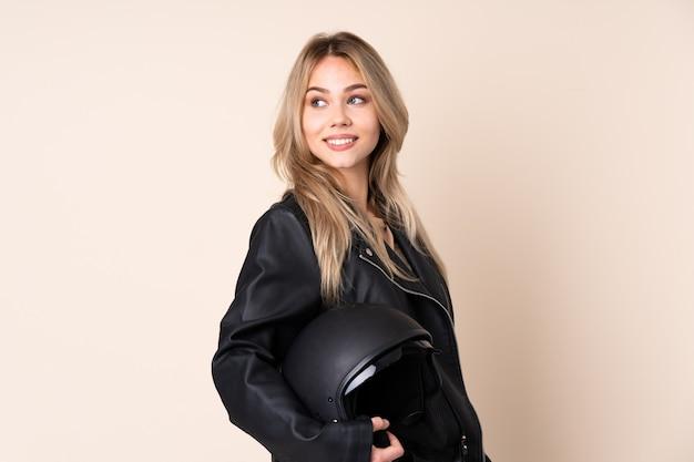 Chica rusa con un casco de moto en la pared de color beige con los brazos cruzados y feliz