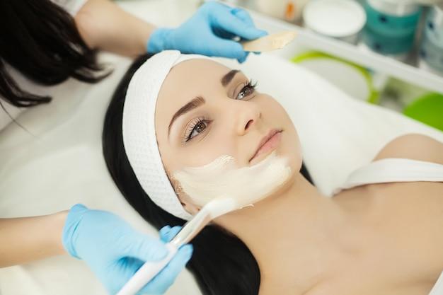 Chica en el salón de spa. esteticista aplicando polvo cosmético blanco