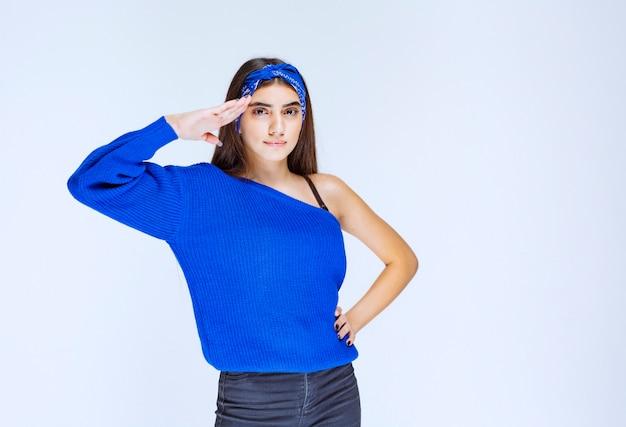 Chica saludando a alguien con un estilo militar.