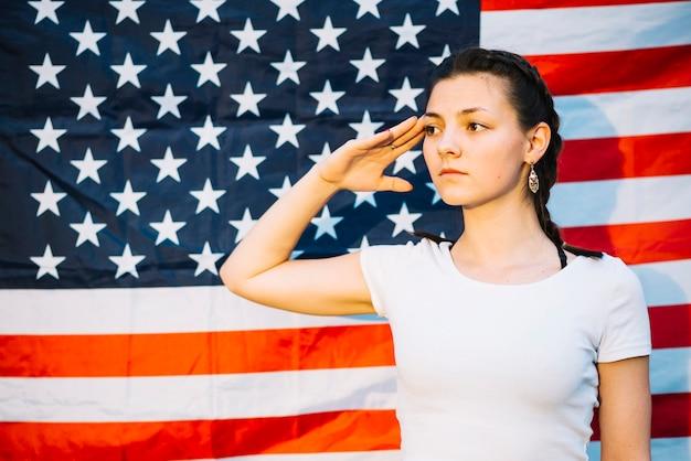 Chica saludando enfrente de bandera americana