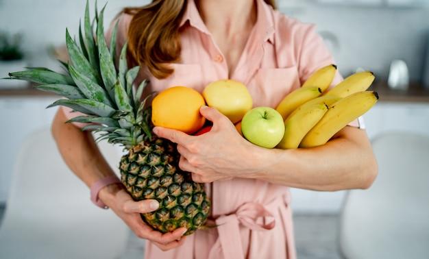 Chica sana con frutas en el fondo de la cocina moderna