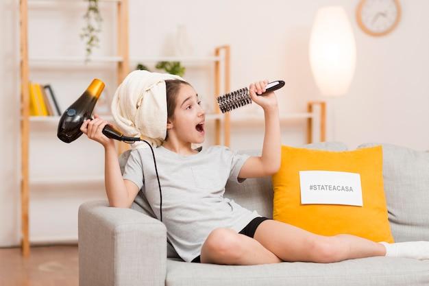 Chica con secador de pelo y cepillo cantando