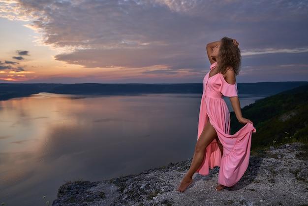Chica seductora posando sobre fondo de paisaje hermoso