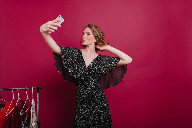 Chica segura con expresión de la cara de besos haciendo selfie en su vestidor. mujer elegante con un pequeño tatuaje en el brazo tomando una foto de sí misma cerca de perchas de ropa.