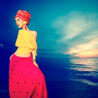 Chica sensual en estilo oriental en la playa al atardecer