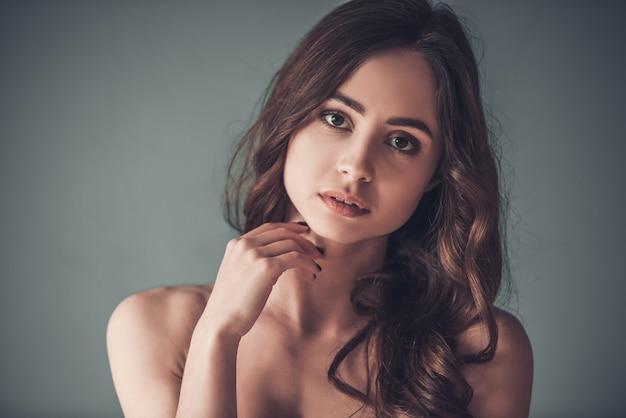 Chica sensual con hombros desnudos mirando a cámara.