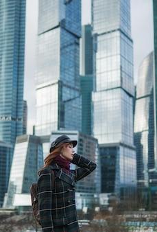 Chica sensual pelirroja en un abrigo y un sombrero negro en los rascacielos de moscú