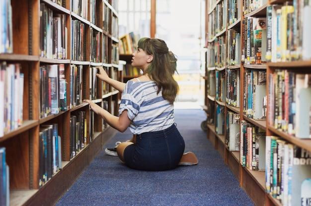 Chica sentada buscando un libro