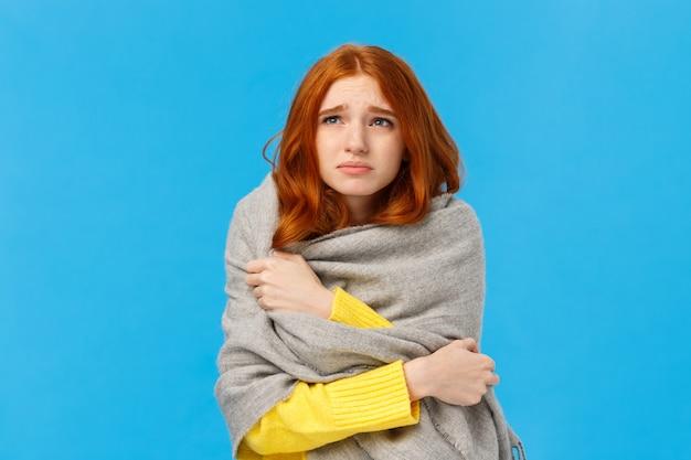 Chica sentada en el dormitorio con calentador roto, envolviéndose con una cálida bufanda