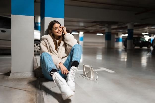 Chica sentada en el estacionamiento subterráneo