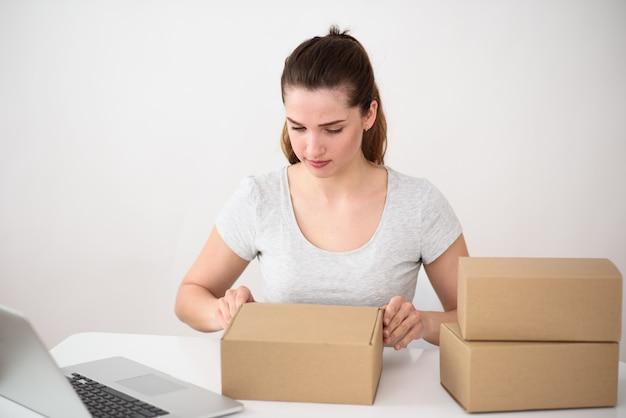 Chica sentada en una mesa de ordenador blanca con un ordenador portátil con interés abre una caja de cartón