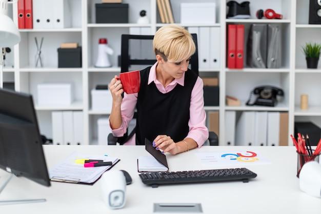 Chica sentada en la oficina en la mesa y tomando café.