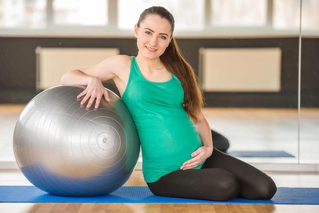 Chica sentada sobre una estera y cogidos de la mano sobre una pelota.