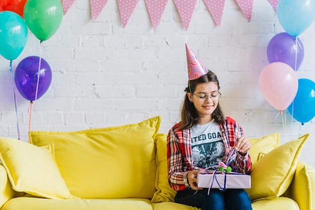 Chica sentada en el sofá desenvolver el regalo de cumpleaños