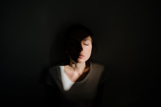 Chica sentada sola en el bolsillo de la luz del sol en el cuarto oscuro. concepto de salud mental