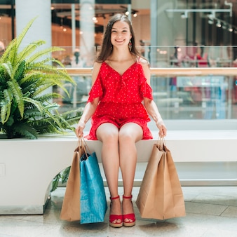 Chica sentada y sosteniendo bolsas de compras
