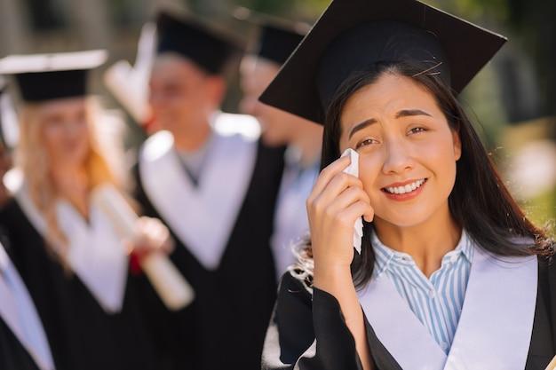 Chica sentimental con gorra de maestro llorando y secándose las lágrimas de las mejillas durante su ceremonia de graduación