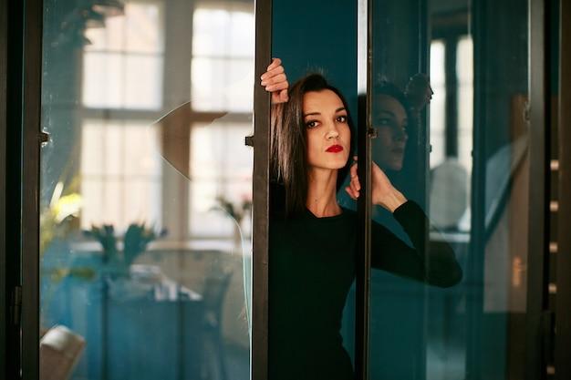 Una chica seria se para cerca de una puerta de vidrio.