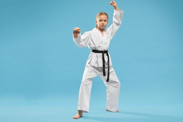 Chica seria en kimono haciendo karate sobre fondo azul.