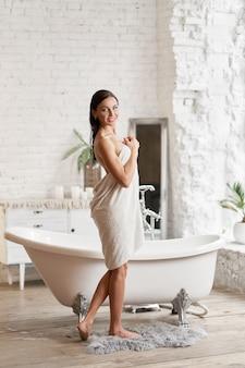 Chica sexy en bata blanca está a punto de bañarse, chica en bata de baño después de bañarse.