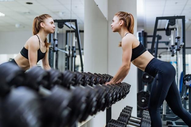 Chica sexy fitness tomando pesas frente al espejo en el gimnasio de deporte.