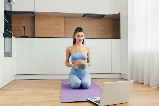Chica sexy haciendo fitness en casa en la cocina