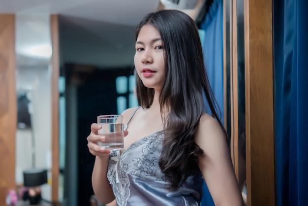 Chica sexy en el hotel, feliz hermosa joven bebiendo agua