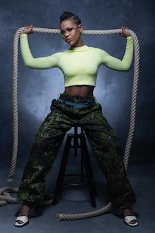 Chica sexy con pantalones de estilo militar y ropa interior de neón posando con una cuerda y mirando a la cámara en el estudio