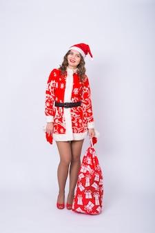 Chica sexy de santa rojo con una gran bolsa de regalos de navidad en la pared blanca.