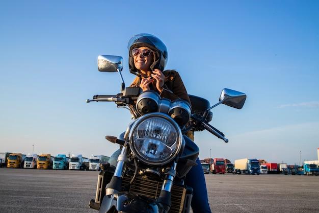 Chica sexy sentada en una motocicleta de estilo retro y abrocharse el cinturón del casco antes de viajar