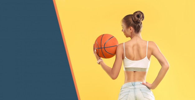 Chica sexy con shorts cortos sosteniendo una pelota de baloncesto en la pared amarilla