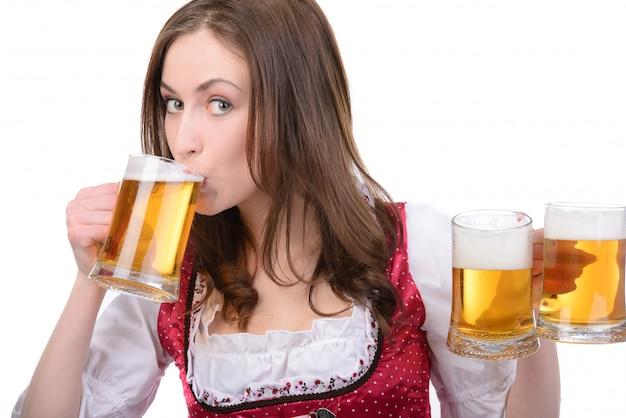 Chica sexy en traje nacional con un vaso de cerveza.