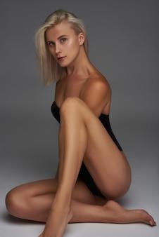 Chica sexy en traje posando en un estudio fotográfico blanco