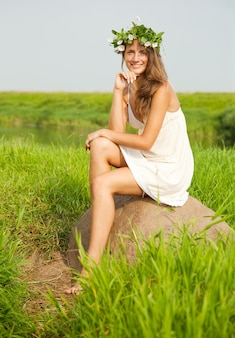 Chica se sienta en el campo de piedra