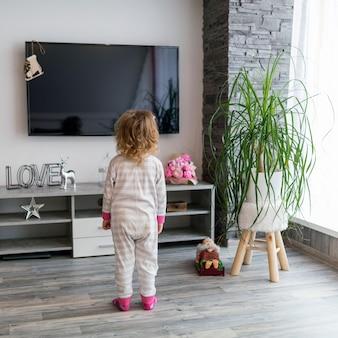 Chica sin rostro mirando televisión