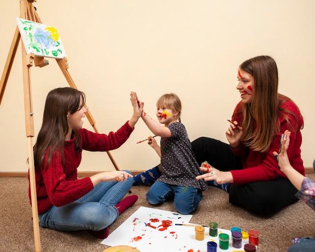 Chica con síndrome de down chocando los cinco mientras pinta