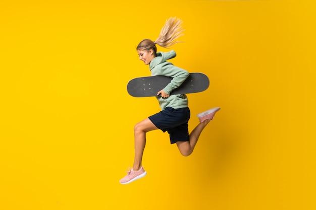 Chica skater adolescente rubia saltando sobre amarillo