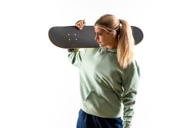 Chica skater adolescente rubia sobre blanco aislado