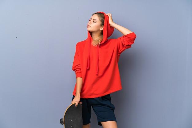 Chica skater adolescente rubia sobre pared gris