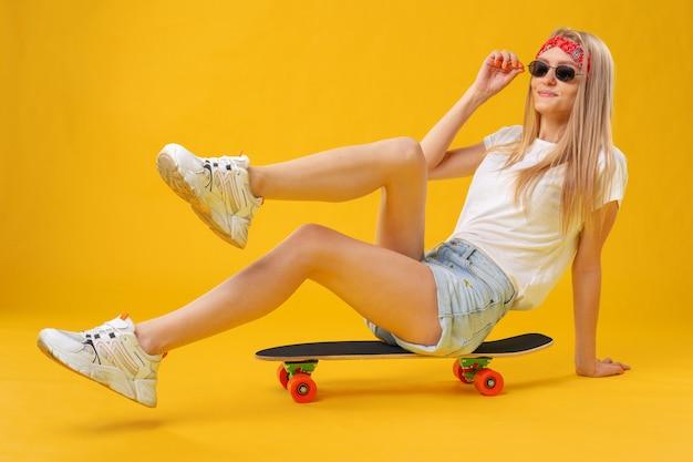 Chica skater en pantalones cortos y camiseta sentada a bordo sobre amarillo