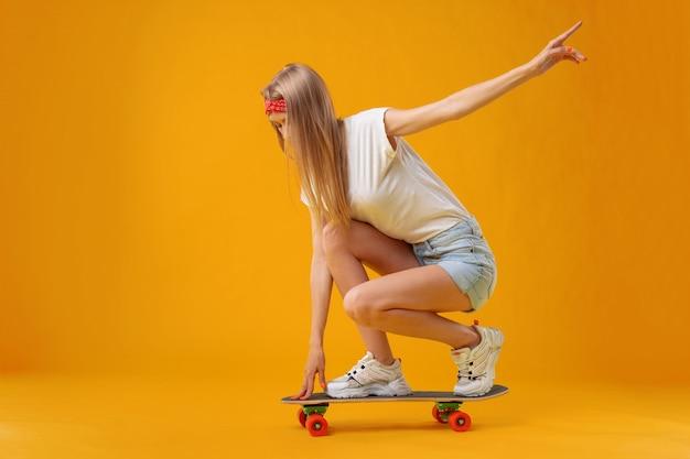 Chica skater en pantalones cortos y camiseta sentada a bordo