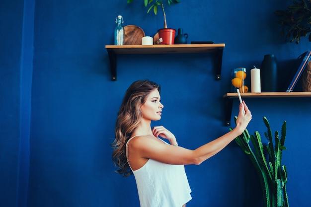Chica con smartphone se divierte y se toma una selfie