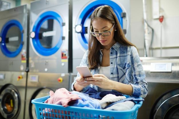 Chica con smartphone en lavandería